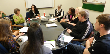 ICEI staff members sit around meeting table and discuss clinic cases.
